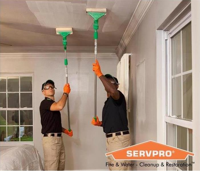 Two SERVPRO techs cleaning up soot from the ceiling.
