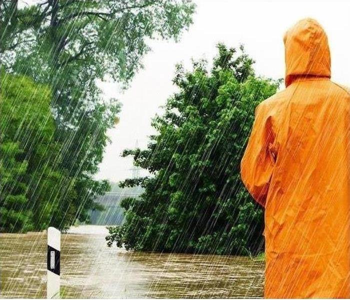 person in orange raincoat in rain with trees and water running